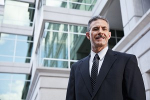 Successful businessman (50s) standing outside building.
